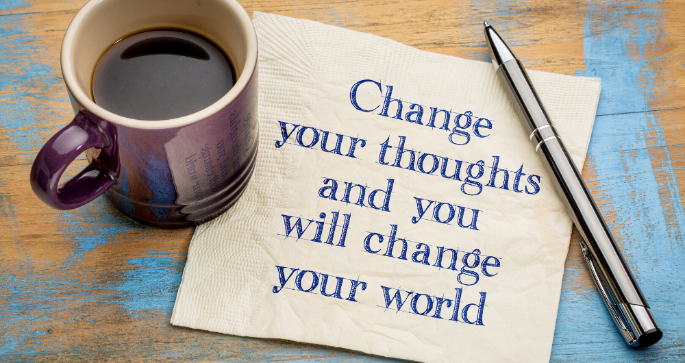 "Cup of coffee with a note beside is saying ""Change your thoughts and you will change your world"""