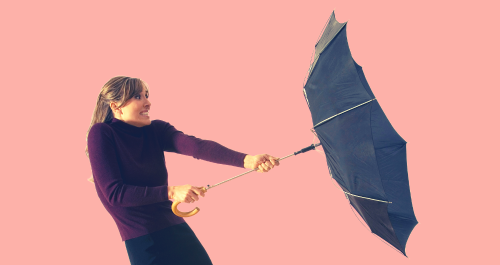 Woman holding on to a wind blown inside out umbrella